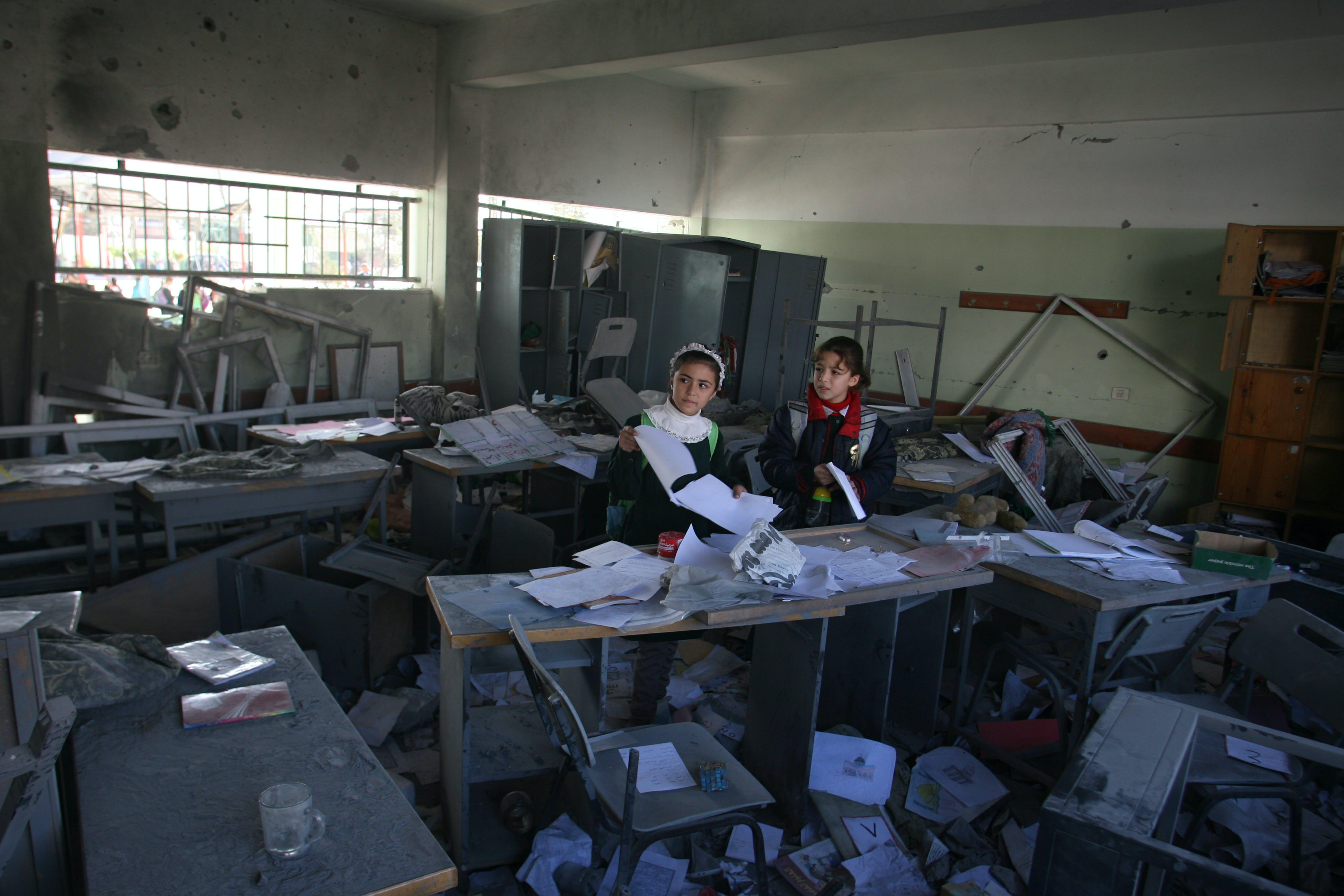 Madlene Abu Dayyeh (12 anni) ispeziona con la sua amica Isra gli effetti di un bombardamento nella scuola femminile Um al-Qura a Gaza City - ©UNICEF/NYHQ2012-1589/ElBaba