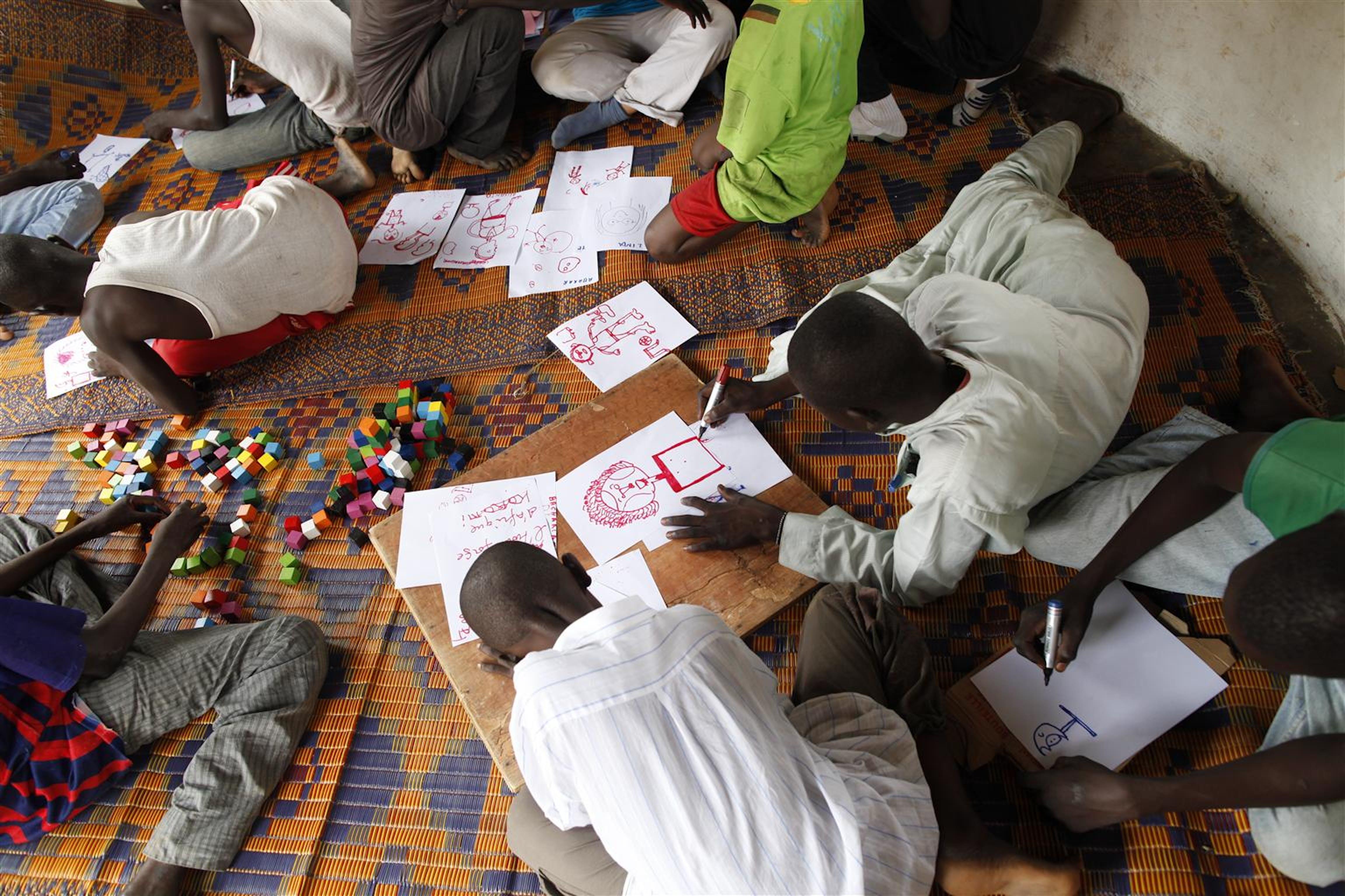 Minori smobilitati dalle milizie armate disegnano e giocano in un Centro di transito finanziato dall'UNICEF a N'dele, nel nord della Repubblica Centrafricana - ©UNICEF/NYHQ2012-1160/Brian Sokol