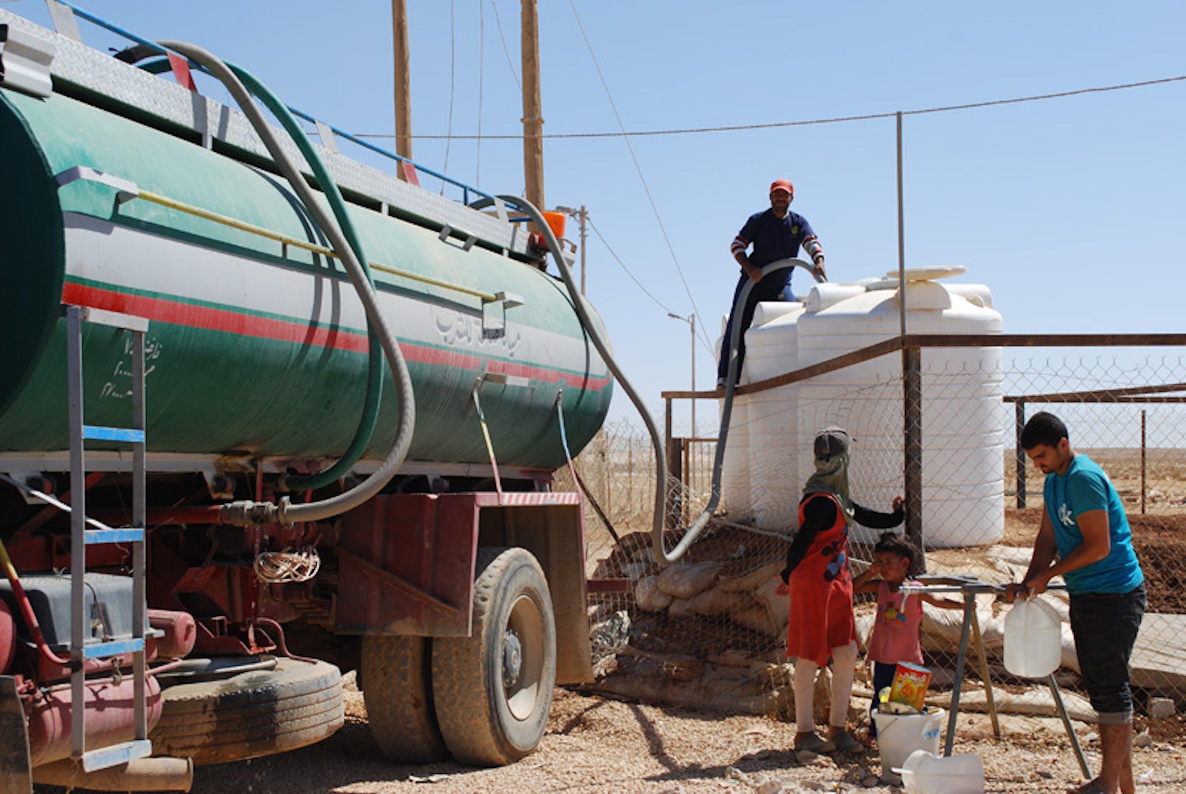 Un'autocisterna rifornisce di acqua potabile alcuni serbatoi del campo profughi di Za'atari, nel deserto della Giordania, che ospita decine di migliaia di siriani - ©UNICEF Giordania/2012/Al Masri