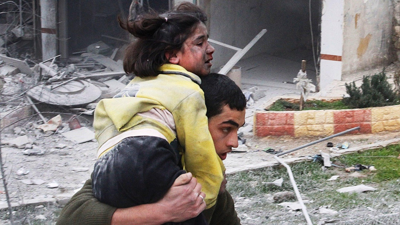Un ragazzo trasporta la sorellina, ferita durante un bombardamento su Ansari, quartiere di Aleppo, febbraio 2013 - ©AP/Abdullah al-Yassin