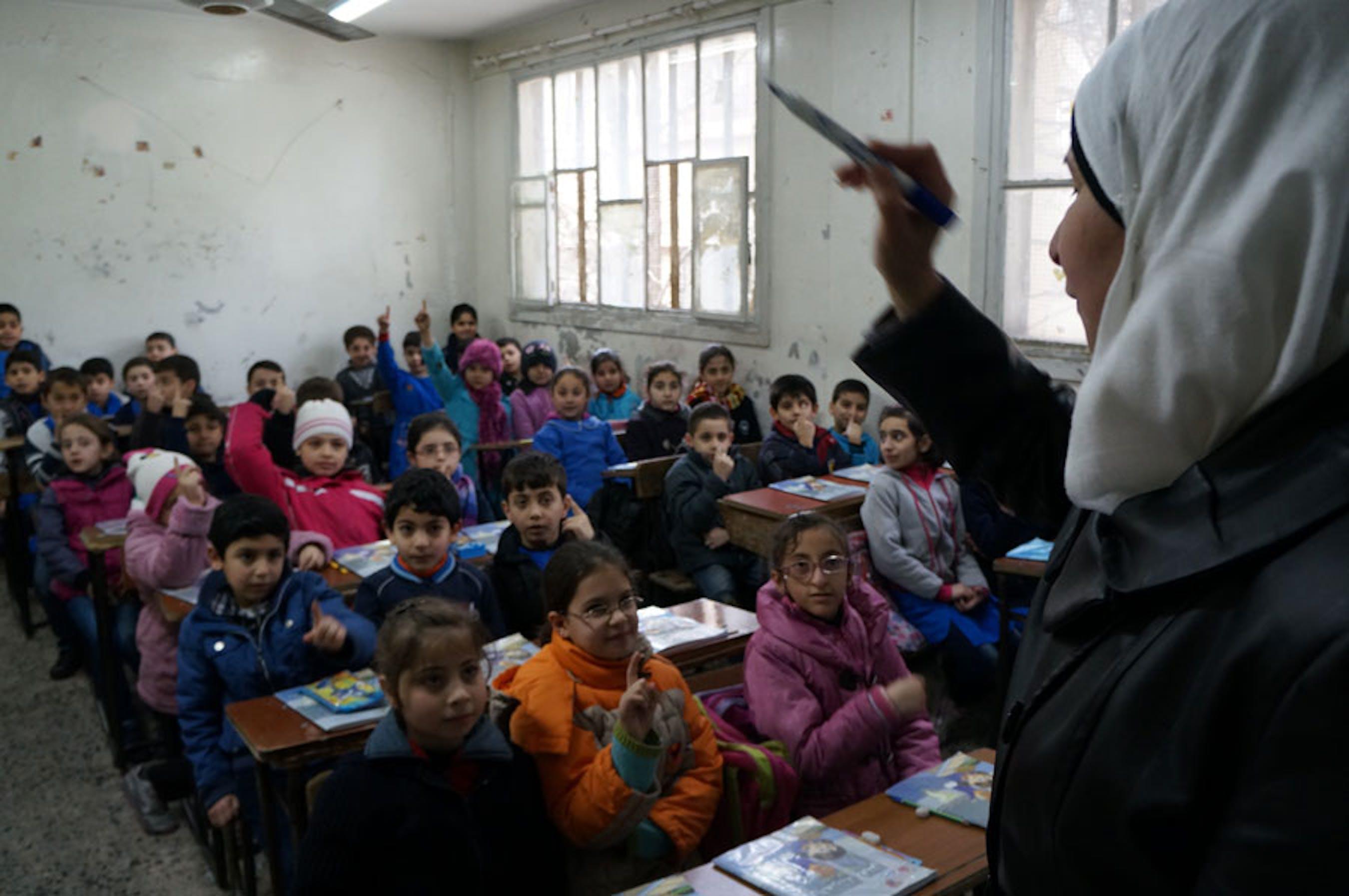 Lezione di lingua araba in una classe sovraffollata a Homs (Siria). La scuola ha ricevuto a febbraio scorte di materiali didattici dell'UNICEF - ©UNICEF Siria/2013/I.Morooka