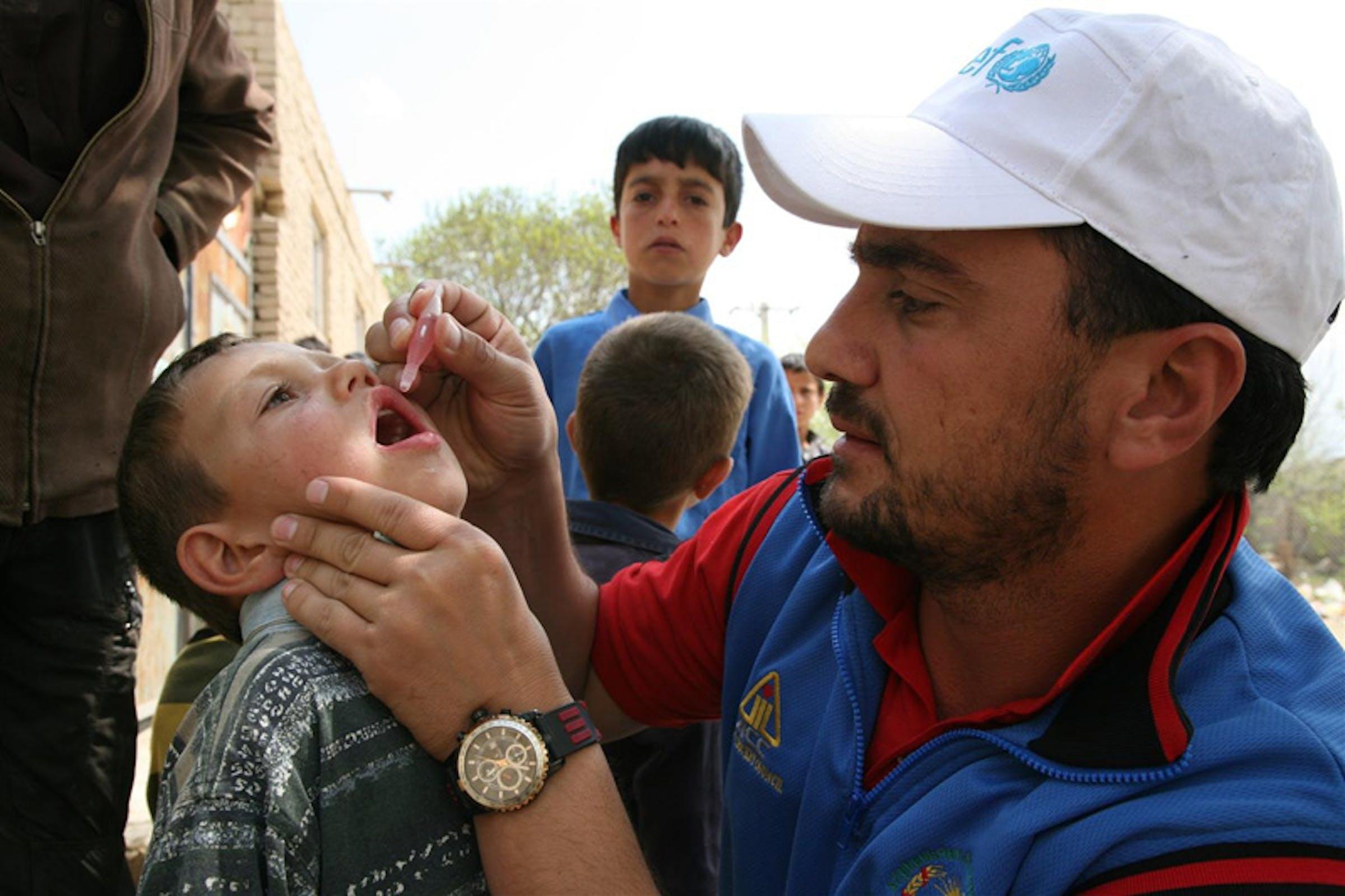 Il campione afgano di cricket e Ambasciatore UNICEF Raees Ahmadzai vaccina un bambino contro la polio durante la Settimana Mondiale delle Vaccinazioni 2012 - ©UNICEF Afghanistan/2012-0038/A.Frutan