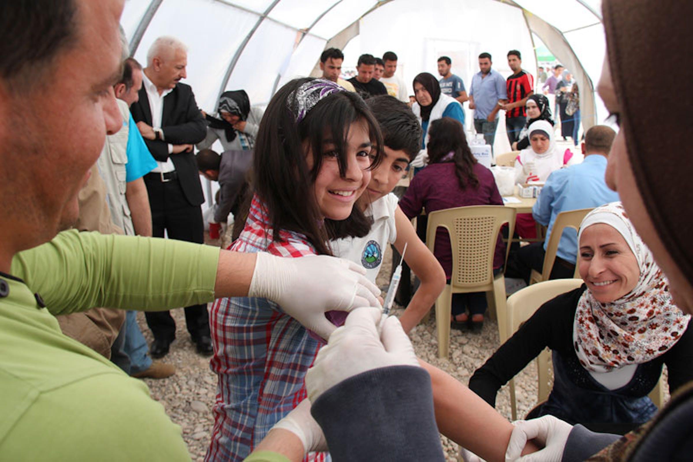 Una ragazza siriana viene vaccinata contro il morbillo nel campo profughi di Domiz, in Iraq - ©UNICEF Iraq/2013/Salam Abdulmanem