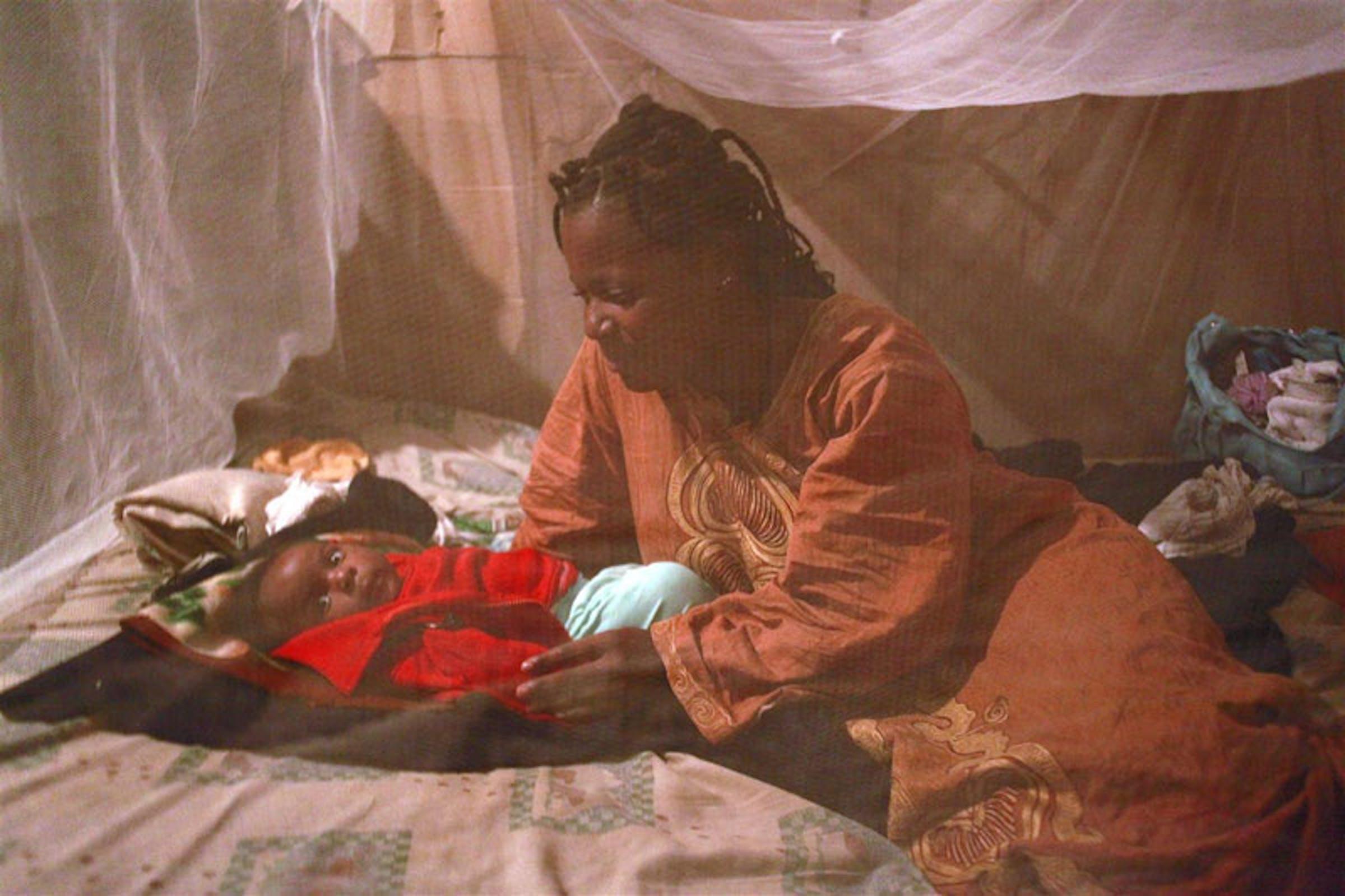 Chance Musigwa insieme al piccolo Marcelin (2 mesi) sotto la nuova zanzariera ricevuta dall'UNICEF nel distretto di Lumumbashi (Repubblica Democratica del Congo) - ©UNICEF RDC/2010-0088/J.Connelly