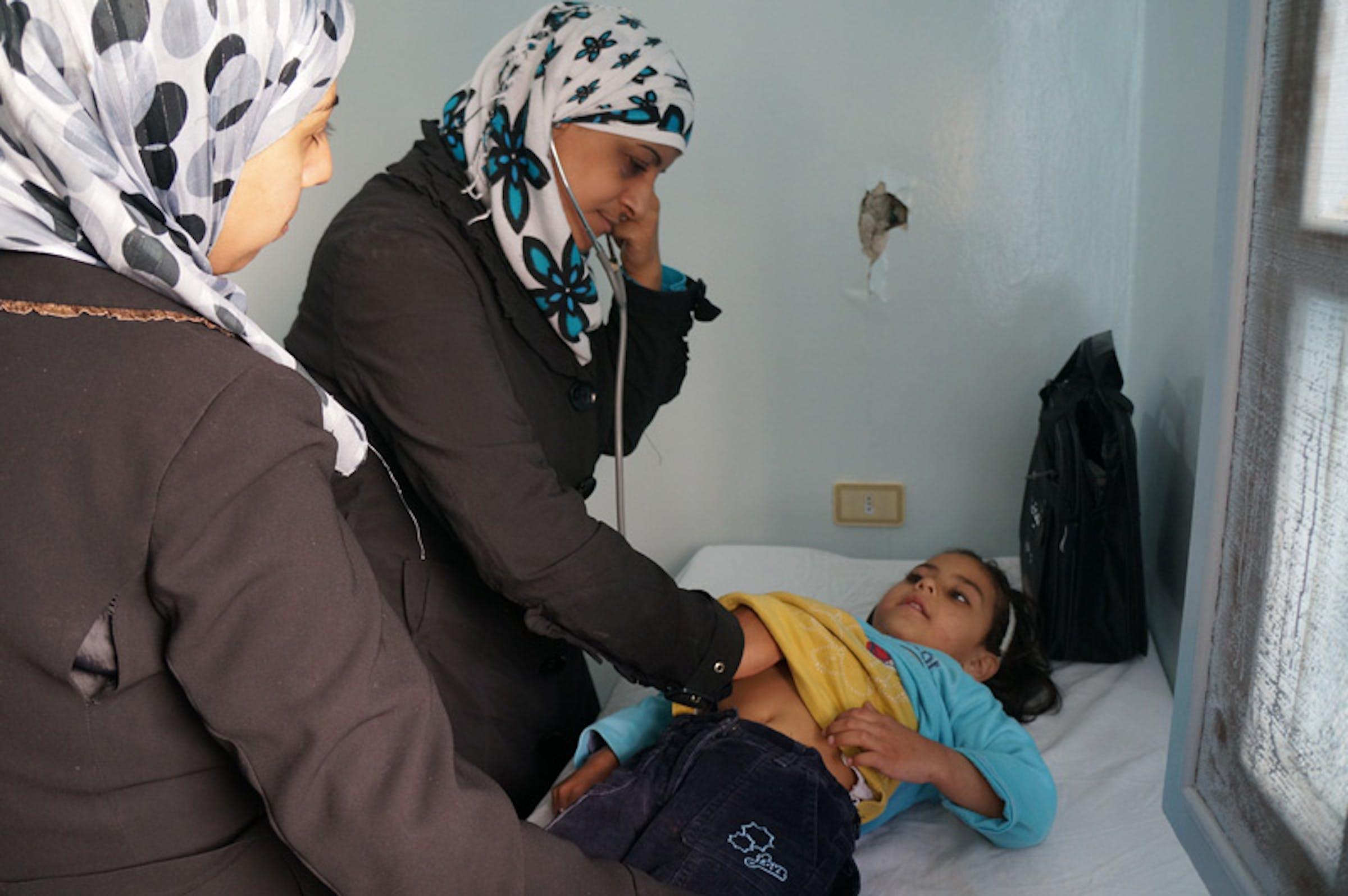Una dottoressa esamina con lo stetoscopio una bambina in un piccolo ospedale di Homs, una delle città più martoriate dalla guerra che da oltre due anni dilania la Siria - ©UNICEF/NYHQ2013-0203/I.Morooka
