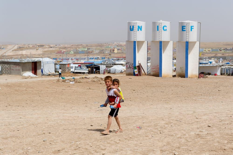 Due bambini camminano di fronte alle cisterne installate dall'UNICEF per garantire nel campo profughi di Domiz, in Iraq, che al momento ospita oltre 43.000 profughi curdi siriani - ©UNICEF Italia/2013-6004/Pino Pacifico