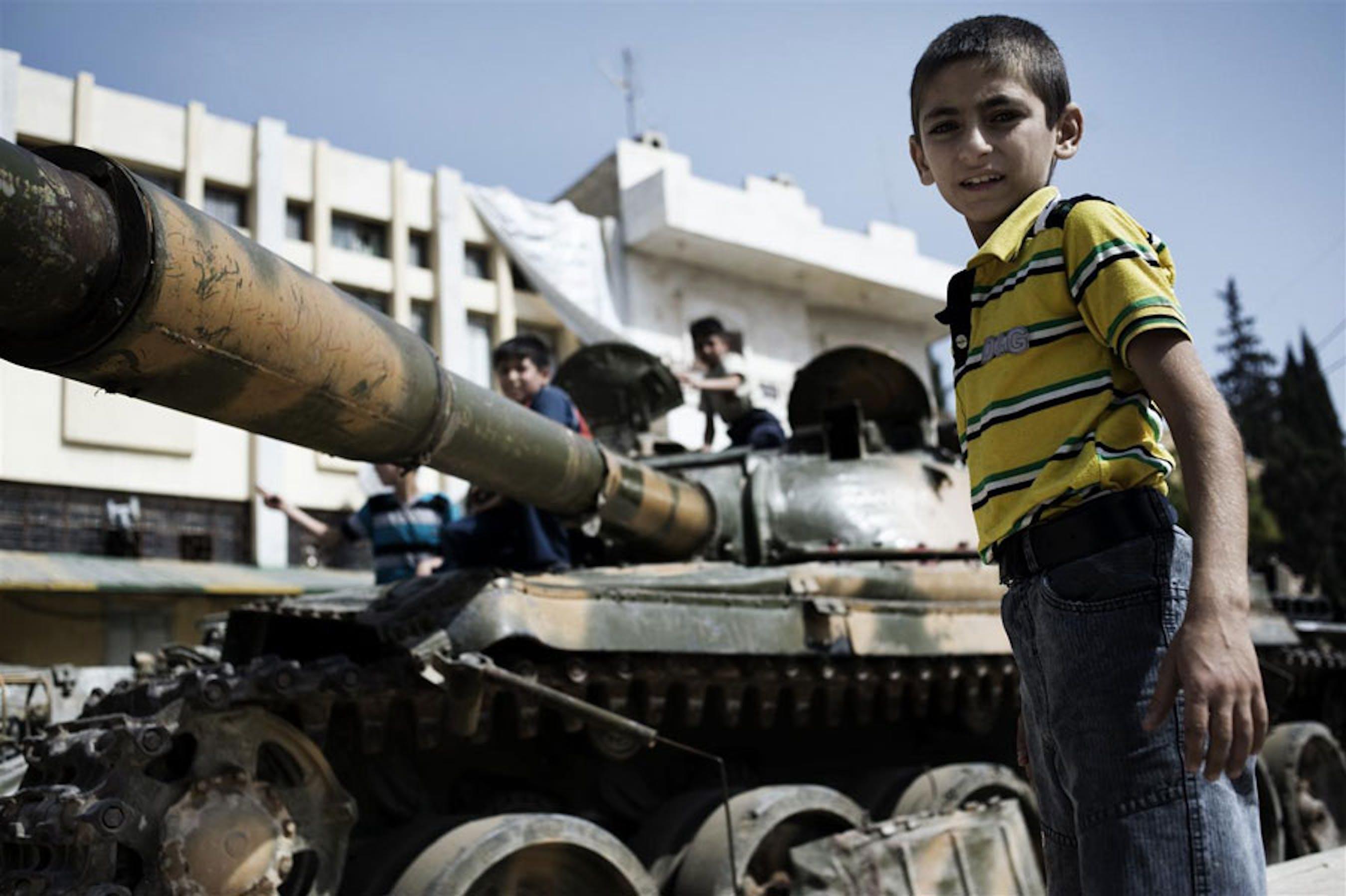 Un bambino accanto a un carro armato in una via di Aleppo, Siria - ©UNICEF/NYHQ2012-1300/Alessio Romenzi