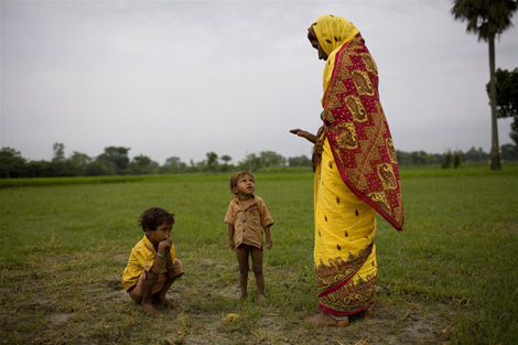 Una donna osserva i suoi bambini mentre defecano in un campo - ©UNICEF India/2008-0065/Adam Ferguson