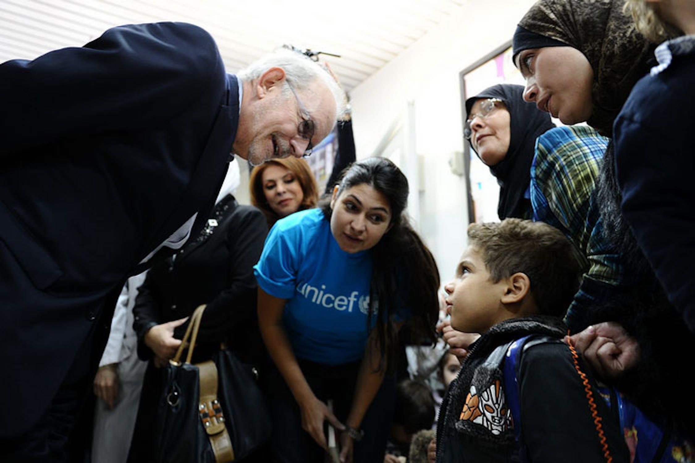 Il direttore UNICEF Anthony Lake parla con un bambino che attende di essere vaccinato nell'ambulatorio di Abu Dhar Al-Ghifari, a Damasco - ©UNICEF/NYHQ2013-0922/Sanadiki