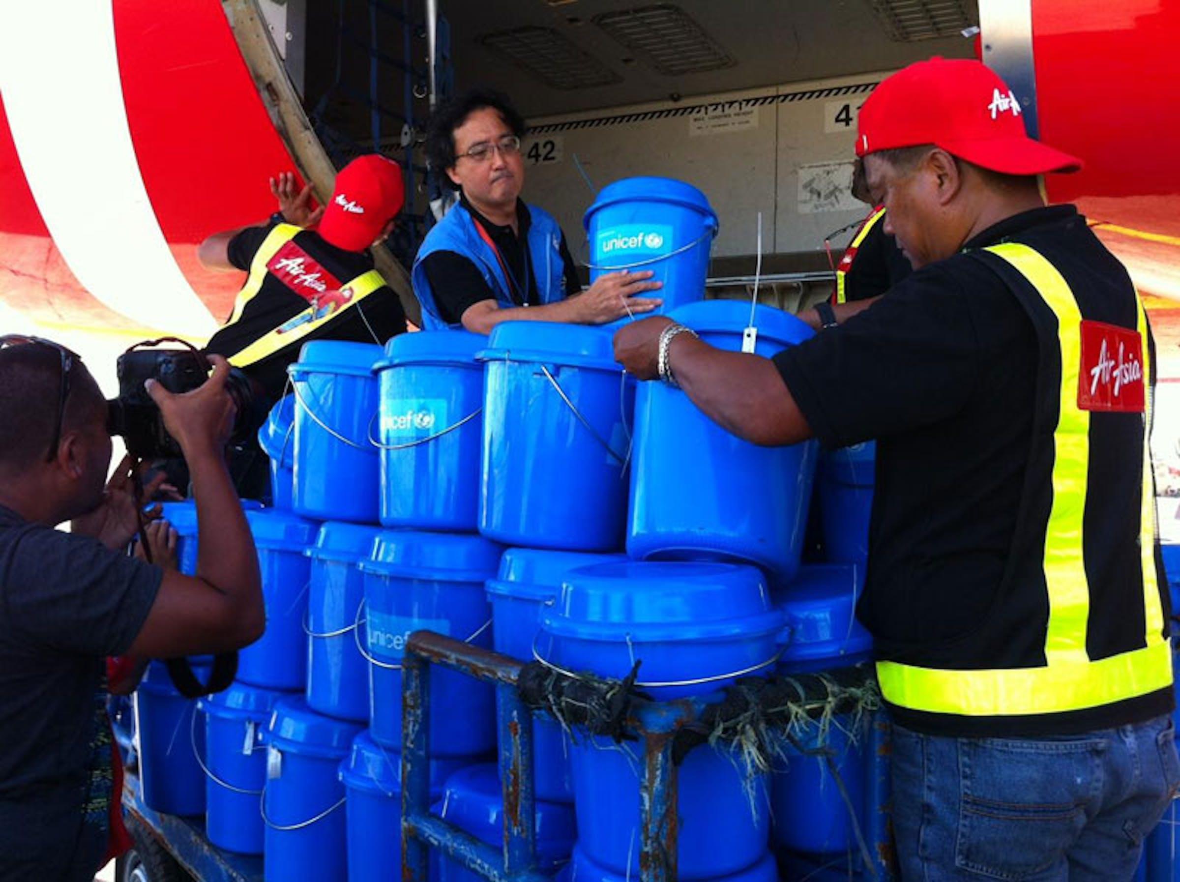 Il Rappresentante UNICEF nelle Filippine Tomoo Hozumi e alcuni operatori caricano scorte di aiuti sul charter umanitario donato a UNICEF da AirAsia - ©UNICEF/PFPG2013P-0246/Marissa Aroy