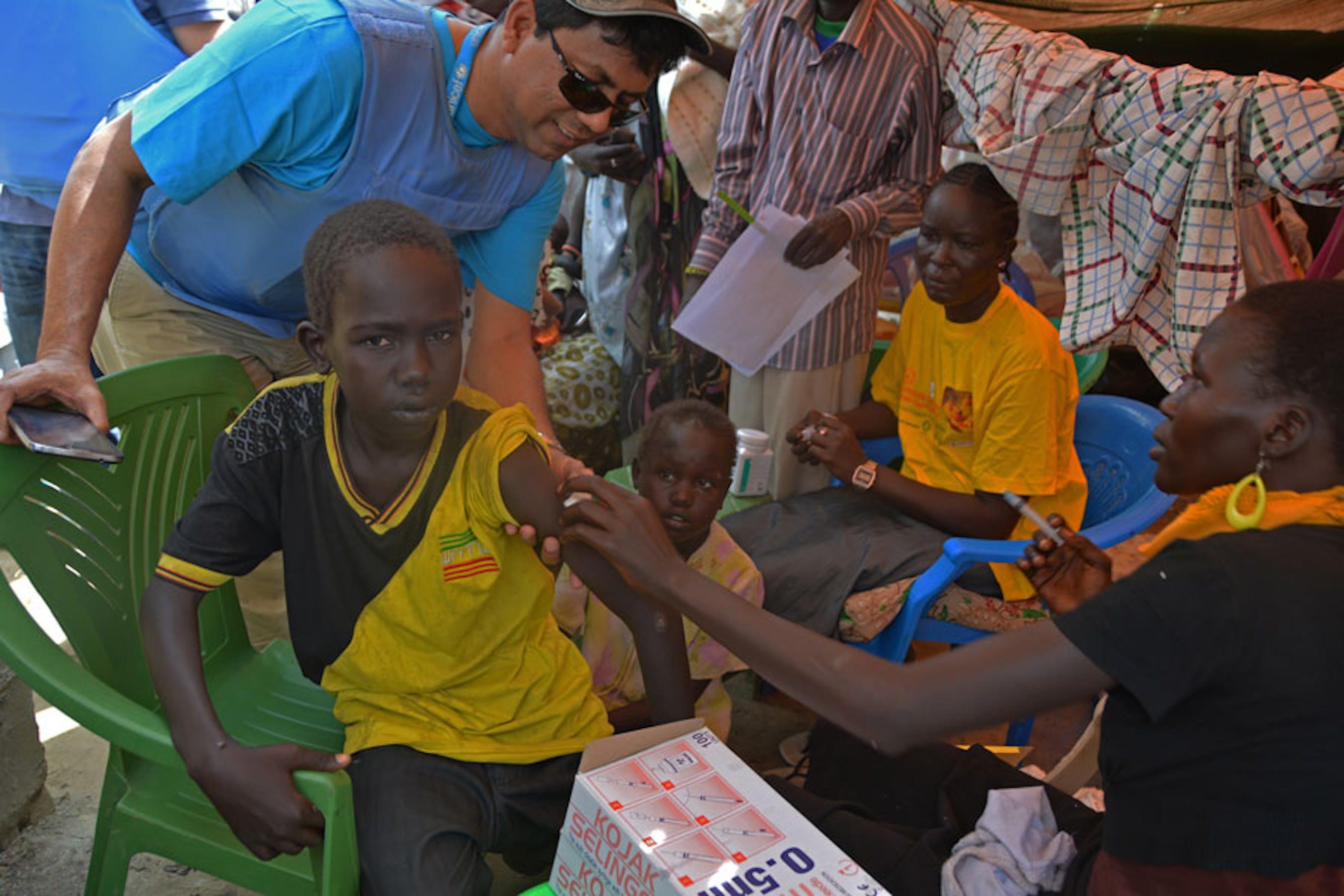 Un operatore sanitario dell'UNICEF impegnato nelle sessioni di vaccinazione contro il morbillo nell'accampamento per sfollati intorno alla base UNMISS a Bor (Sud Sudan) - ©UNICEF/NYHQ2014-0086/Sarah Crowe