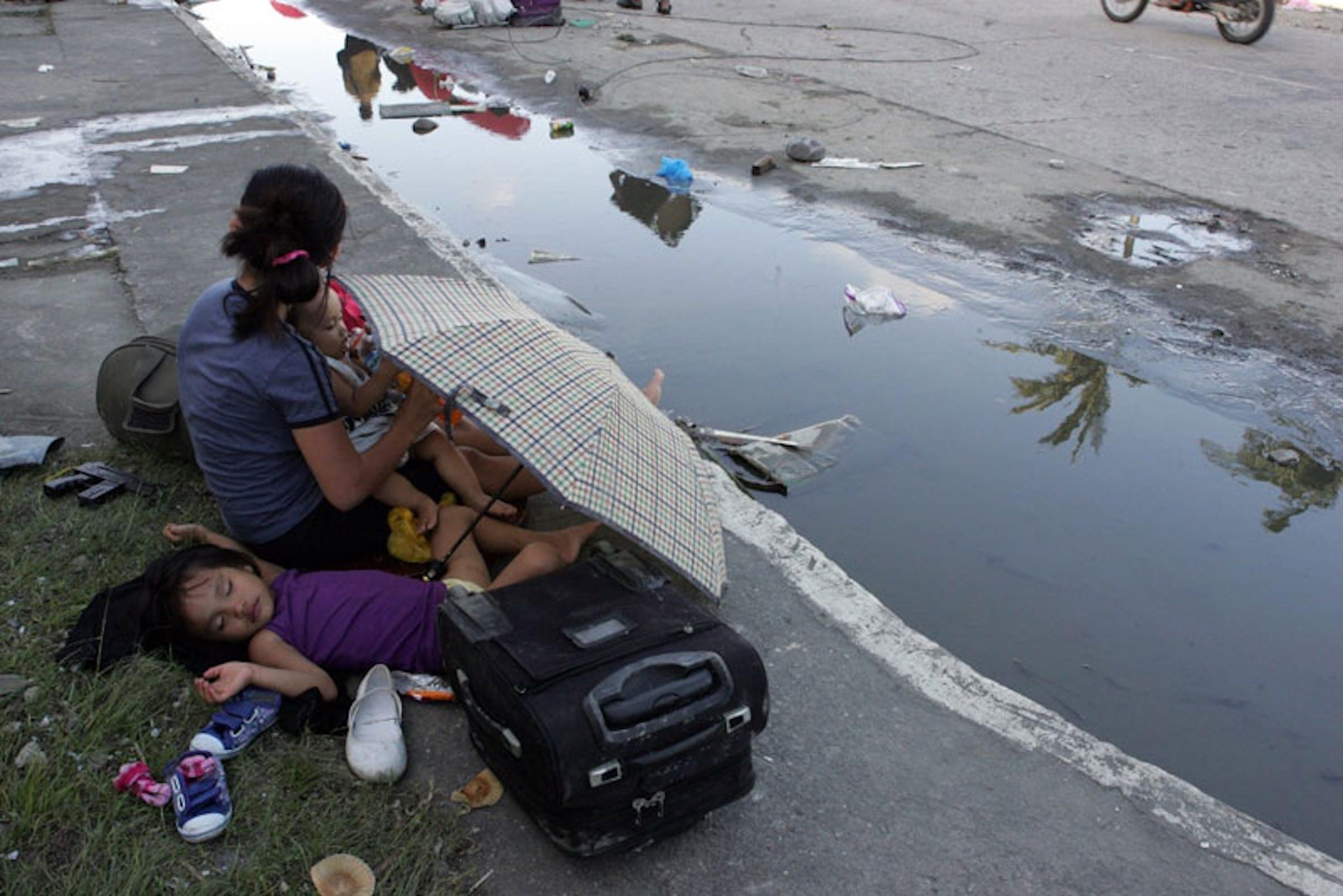 Madre e figli a Tacloban City, Filippine. Sono almeno 100.000 i bambini sotto i 5 anni senza tetto nelle aree colpite dal tifone Haiyan - ©UNICEF/NYHQ2013-0995/J.Maitem
