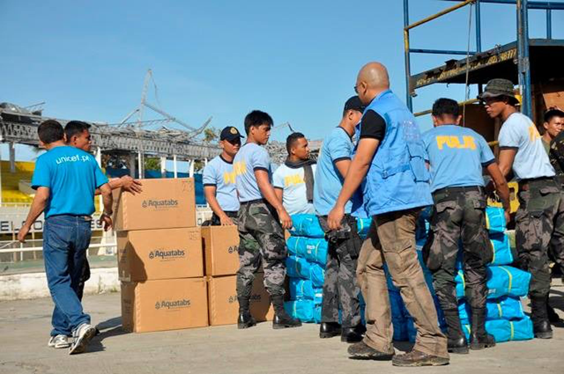 Militari e operatori civili scaricano scorte di sostanze per potabilizzare l'acqua fornite dall'UNICEF nella città di Roxas - ©UNICEF Filippine/2013/Ivan Hibalo