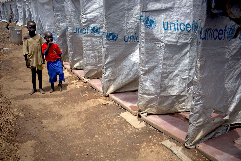 Bambini accanto a una serie di latrine installate dall'UNICEF intorno alla base militare di Tomping (Sud Sudan) dove si sono rifugiati migliaia di sfollati - ©UNICEF/NYHQ2014-0337/Holt