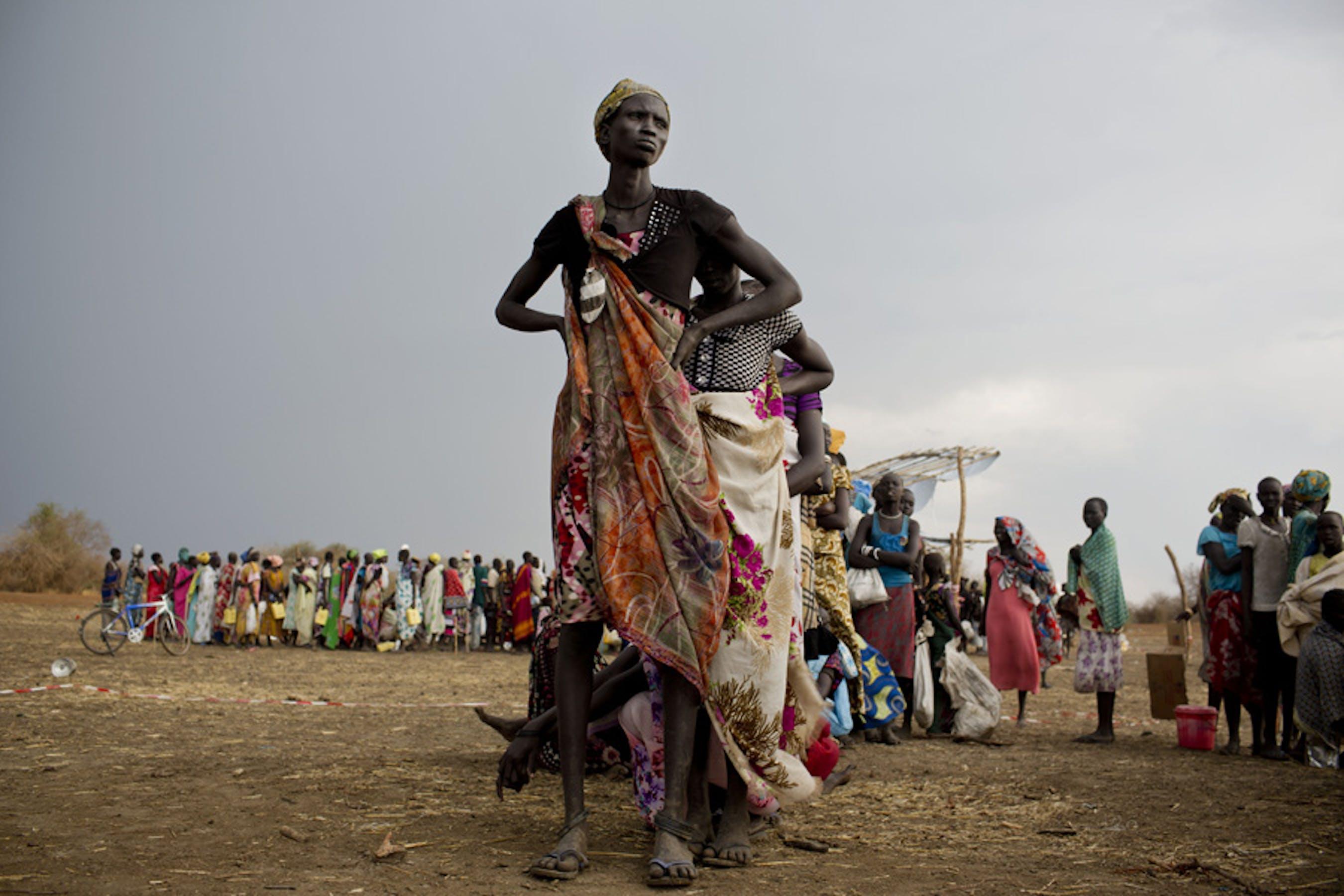 Donne e bambini fanno la fila per la distribuzione di razioni alimentari in un punto di distribuzione di aiuti alimentari a Mingkaman (Sud Sudan) - ©UNICEF/NYHQ2014-0349/Holt