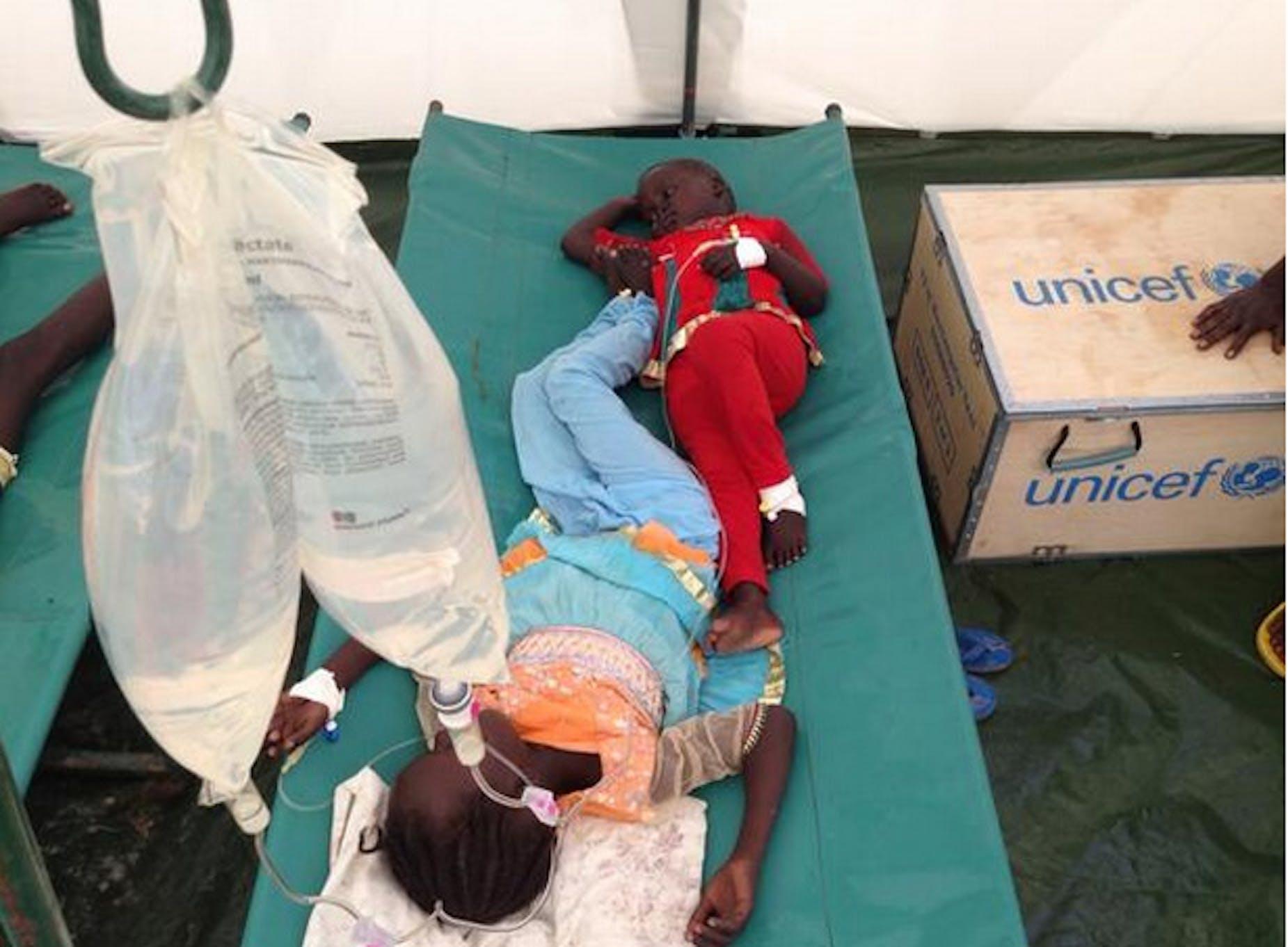 Due sorelline di 4 e 7 anni ricevono la fluidoterapia per la cura del colera all'interno di una tenda-ospedale allestita dall'UNICEF a Juba (Sud Sudan) - ©UNICEF/2014/Kent Page