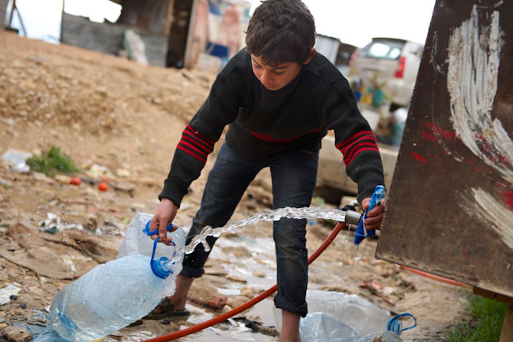 Un bambino riempie una tanica di acqua dalla cisterna installata dall'UNICEF nel campo profughi di Baalbek (Libano) - ©UNICEF Libano/2013/Shehzad Noorani