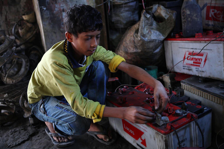 Al Amin, 10 anni, ripara le batterie degli autobus in un garage della stazione dei bus di Tangail (Bangladesh) - ©UNICEF Bangladesh/2014-00249/Shafiqul Alam Kiron