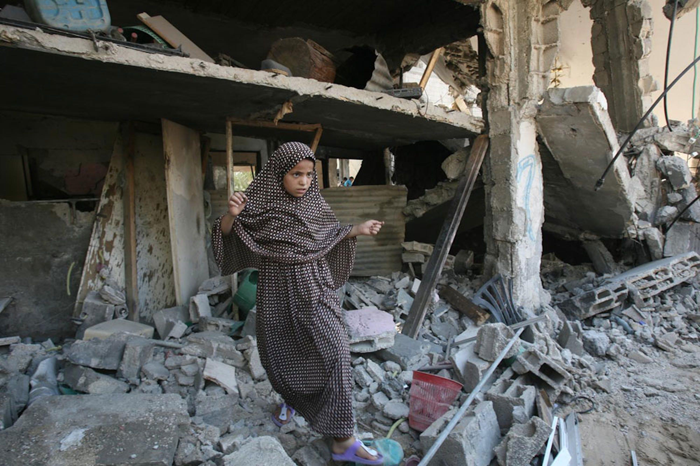 Una bambina palestinese fra le macerie della sua casa distrutta da un attacco aereo a Khan Yunis, nel sud della Striscia di Gaza - ©UNICEF/NYHQ2014-0895/Iyad El Baba