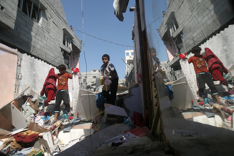 Bambini palestinesi recuperano alcuni vestiti dalle macerie della loro abitazione nel campo profughi di Khan Younis, nel sud della Striscia di Gaza - ©UNICEF/NYHQ2014-0905/Iyad El Baba