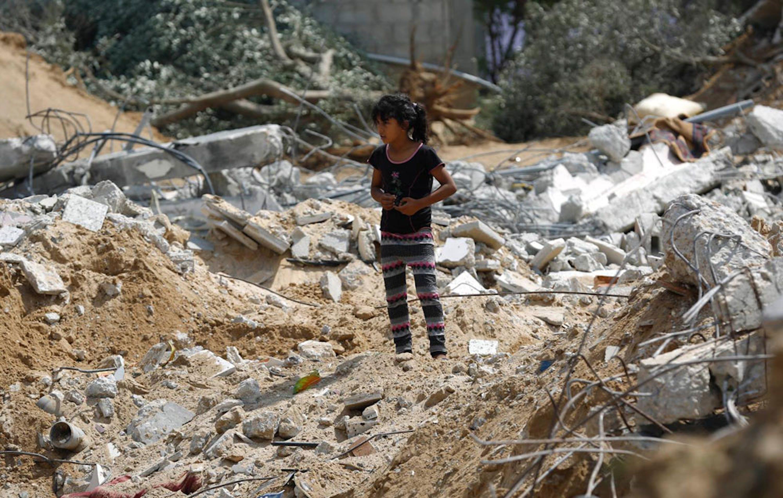 Una bambina fra le macerie della palazzina di tre piani in cui viveva, nella città di Khan Yunis (nel sud della Striscia di Gaza), rasa al suolo da un raid israeliano il 20 luglio scorso - ©UNICEF/NYHQ2014-1003/Iyad El Baba