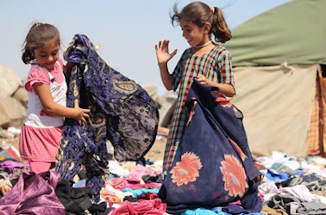 Due bambine rifugiate stanno setacciando tra mucchi di vestiti arrivati presso il campo Nawrouz, cercando di trovare le taglie adatte a loro. ©UNICEF/Syria-2014/Rashidi