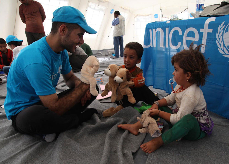 Un operatore UNICEF gioca con due bambini in un centro per sfollati a Peshkhabaour (Iraq). Quasi 4 milioni di bambini di questa età sono stati vaccinati contro la polio in soli 5 giorni - ©UNICEF/NYHQ2014-1177/Khuzaie