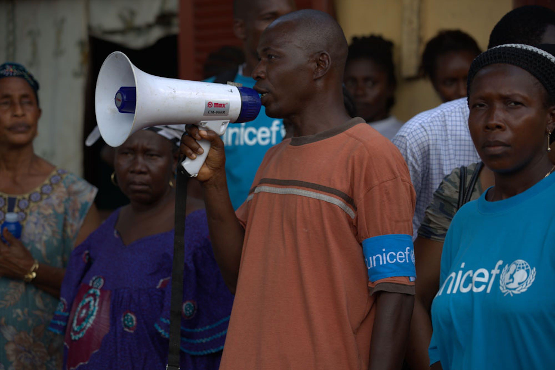 Volontari della ONG locale AJCOM impegnati in un'attività di informazione pubblica su come evitare il contagio di Ebola in una piazza di Conakry (Guinea). L'attività è svolta sotto l'egida dell'UNICEF - ©UNICEF/NYHQ2014-1529/Timothy La Rose