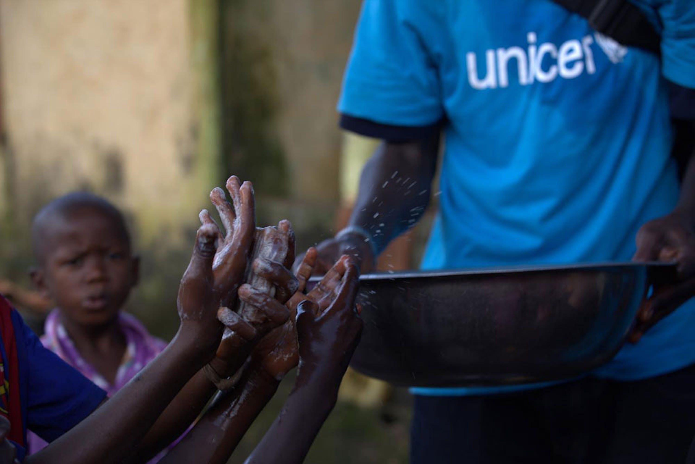 Un volontario di un'associazione locale partner dell'UNICEF impegnato in un'attività di educazione all'igiene con i bambini a Conakry (Guinea) - ©UNICEF/NYHQ2014-1522/LaRose