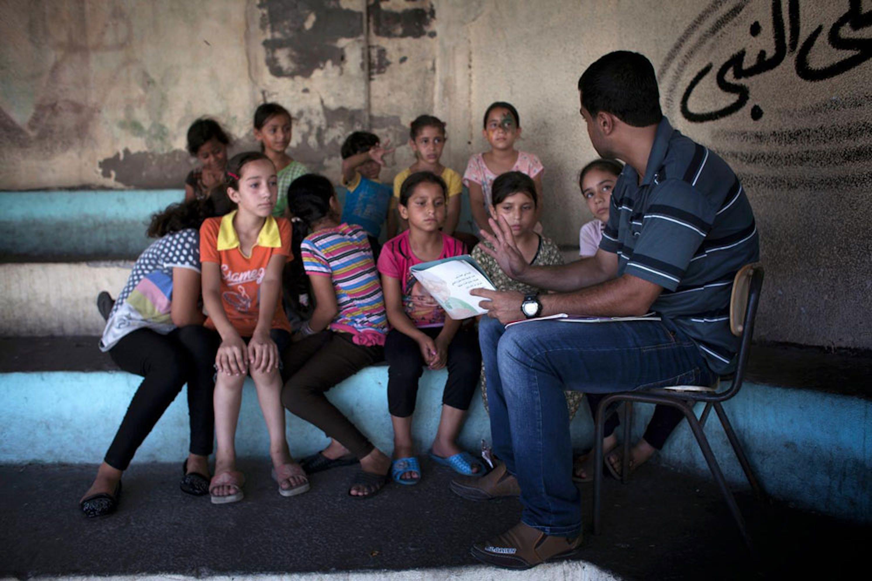 Un volontario legge una storia a un gruppo di bambini sfollati insieme alle loro famiglie in una scuola di Gaza. La foto è stata scattata il 25 agosto, alla vigilia del cessate il fuoco dopo 50 giorni di guerra - ©UNICEF/NYHQ2014-1439/Loulou d'Aki