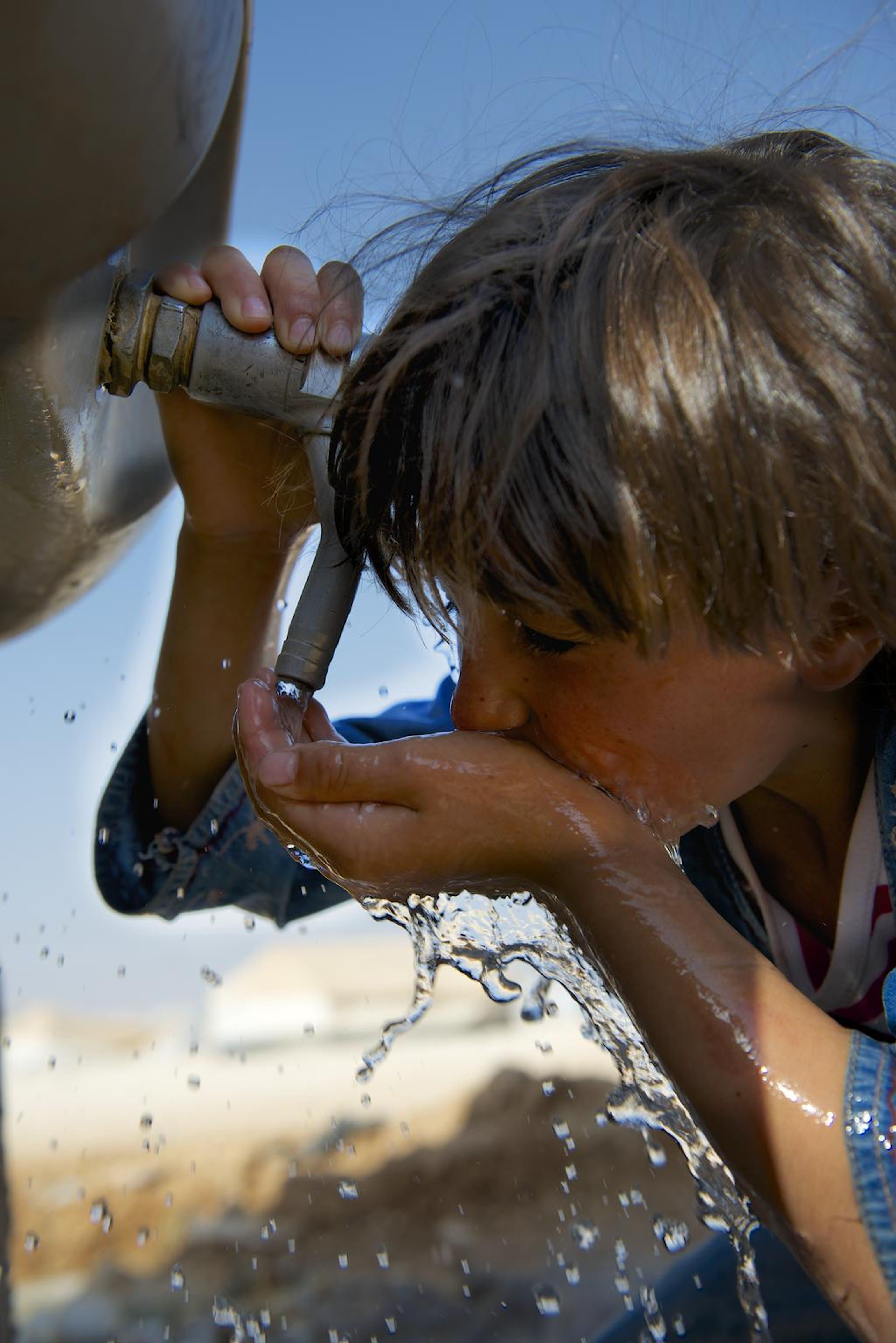 Una bambina siriana si disseta da una cisterna installata dall'UNICEF nel campo profughi di Za'atari, in Giordania - ©UNICEF/NYHQ2013-0667/Noorani