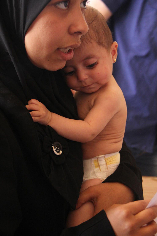 Una mamma con la sua bambina, affetta da malnutrizione, sotto terapia in un centro nutrizionale di Aleppo, finanziato dall'UNICEF - ©UNICEF/NYHQ2014-3066/Rashidi