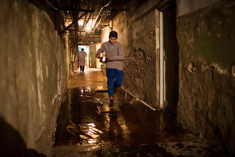 Un ragazzo trasporta di corsa il pasto della sua famiglia, che da mesi vive nei sotterranei di un palazzo a Donetsk con gravissimi problemi igienici e di umidità - ©UNICEF/NYHQ2014-3505/Francesca Volpi