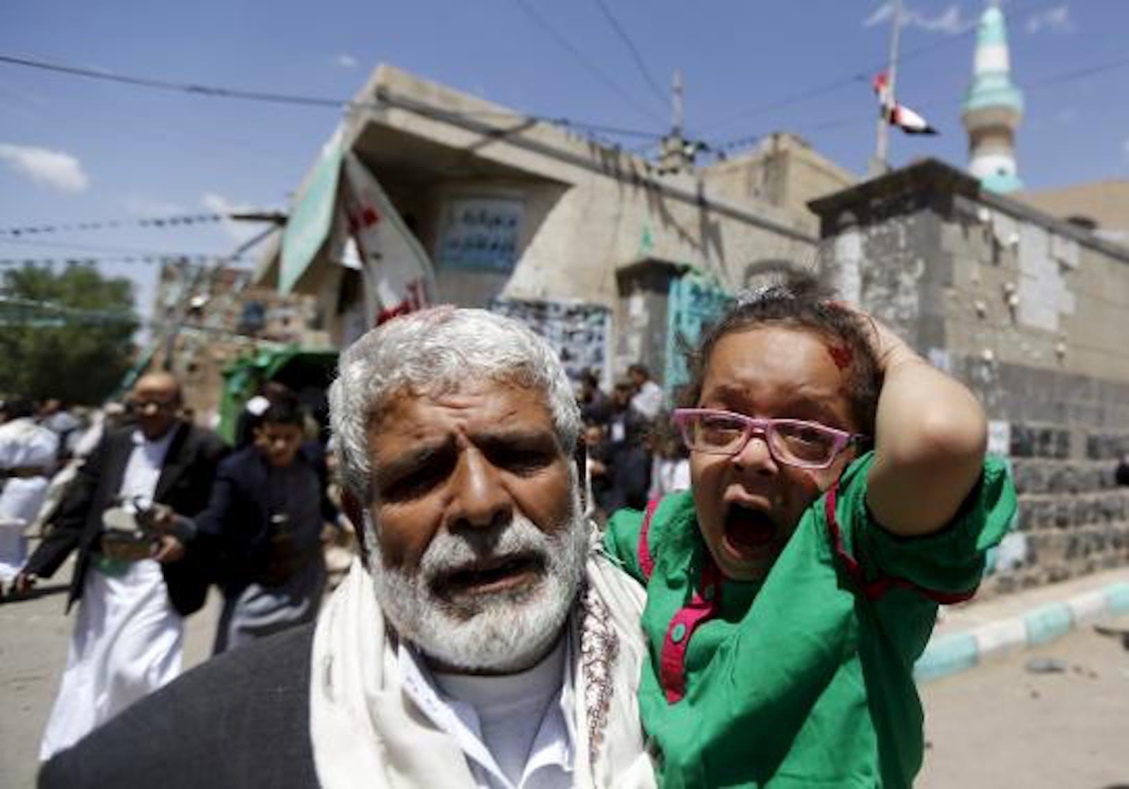 Una bambina terrorizzata e ferita viene portata via da una delle due moschee di Sana'a colpite dagli attentatori kamikaze il 20 marzo 2015 - ©IINAnews.com