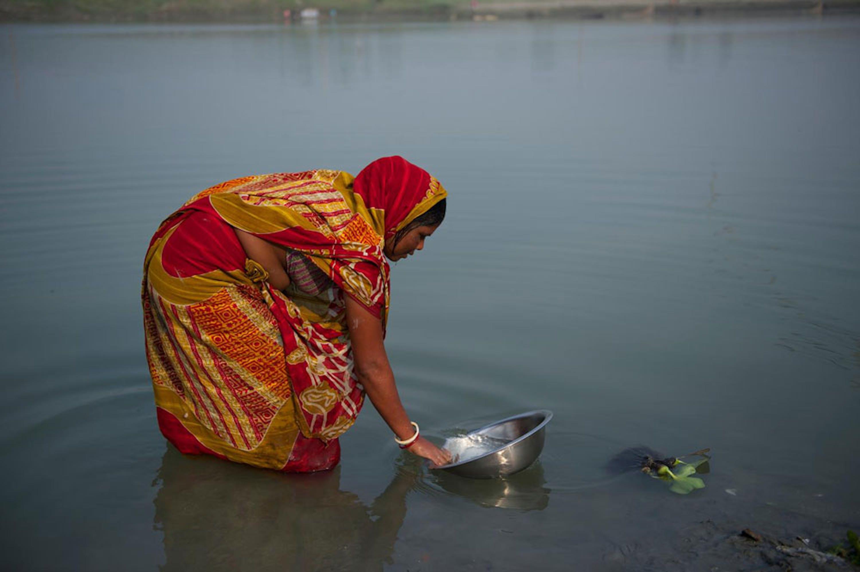 Una donna lava le stoviglie in un fiume del distretto di Jamalpur, Bangladesh - ©UNICEF/NYHQ2014-3287/Noorani