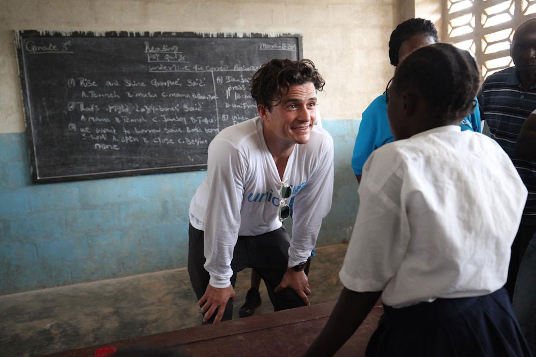 Orlando Bloom si intrattiene con una studentessa durante la sua visita alla scuola pubblica di Jene Wonde, una township nel nord della Liberia. In questo villaggio Ebola ha ucciso più di 40 abitanti - ©UNICEF/NYHQ2015-0459/Jallanzojpg