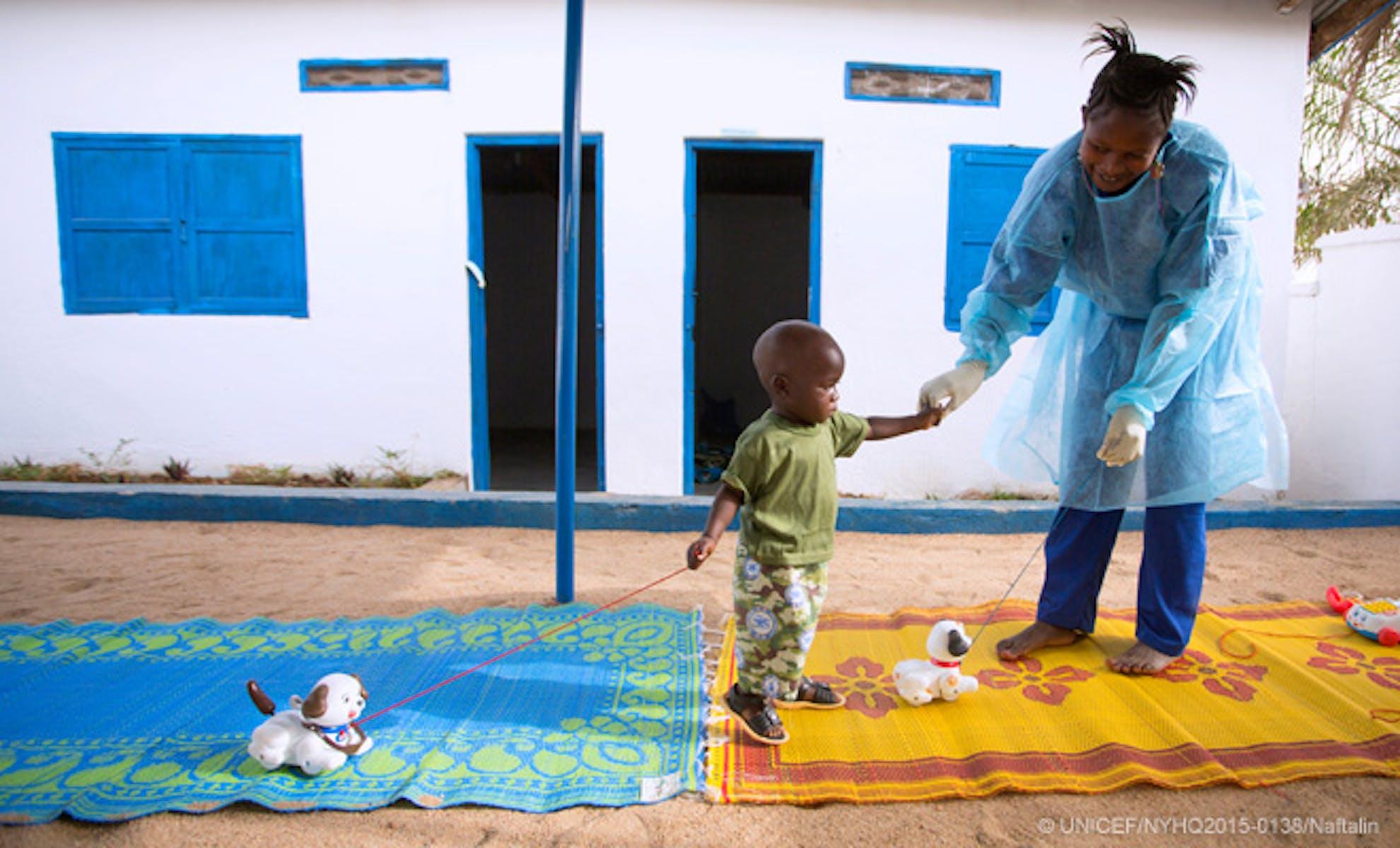 Bambino e infermiera in un centro di isolamento per sospetti casi di Ebola in Guinea. Il centro è sostenuto economicamente e tecnicamente dall'UNICEF - ©UNICEF/2015