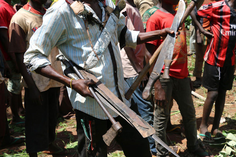 Un miliziano del gruppo anti-Balaka raccoglie fucili e machete nel corso di una cerimonia di smobilitazione di