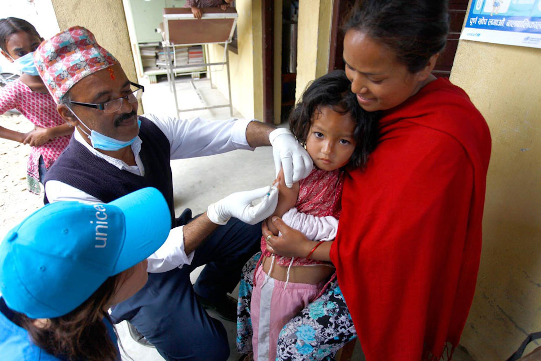 Neisha, 4 anni, viene vaccinata contro il morbillo. Dal giorno del terremoto Neisha e la sua famiglia vivono all'aperto, in una fattoria nel villaggio di Bungamati (Nepal) - ©UNICEF/NYHQ2015-1107/Panday
