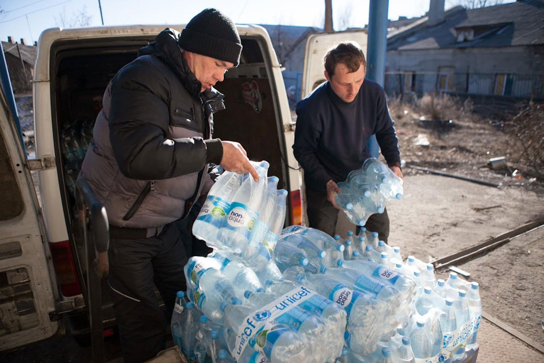 Una scena frequente da mesi, nell'est dell'Ucraina: volontari UNICEF distribuiscono acqua in una zona teatro di combattimenti - ©UNICEF/NYHQ2015-0279/Filippov