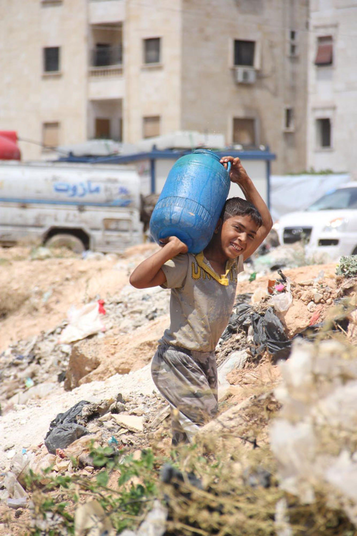 Un bambino trasporta un bidone di acqua a Tishreen, un campo per sfollati nella città di Aleppo (Siria) - ©UNICEF/NYHQ2014-3061/Rashidi