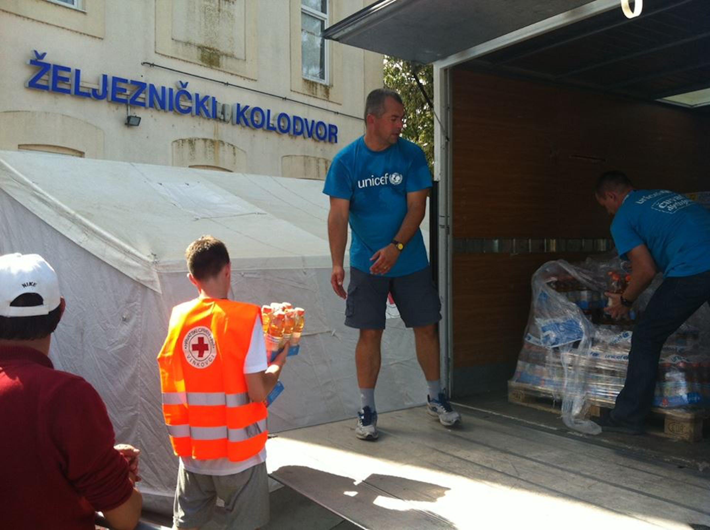 Volontari dell'UNICEF Croazia scaricano acqua, pannolini e altri beni di prima necessità per le famiglie in transito nel paese - ©UNICEF Croazia/2015/Marin Ilej