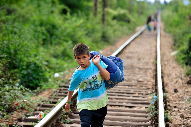 Un bambino trasporta i suoi averi lungo la ferrovia al confine tra Serbia e ex repubblica jugoslava di Macedonia - ©UNICEF/NYHQ2015-2203/Georgiev