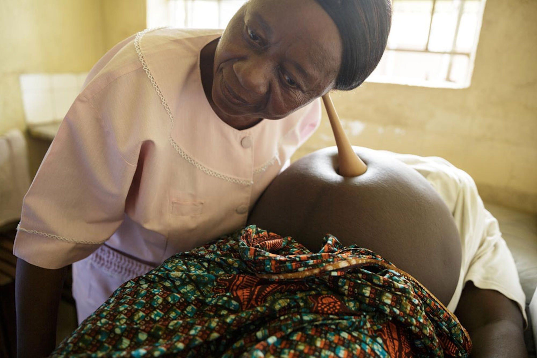 Un'ostetrica controlla il battito fetale durante una visita prenatale nell'ospedale di Kenema, in Sierra Leone. La struttura sanitaria è stata finanziata in larga parte dai donatori italiani dell'UNICEF - ©UNICEF Sierra Leone/2013-0579/Asselin