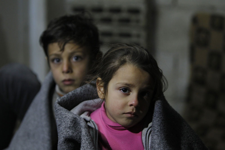 Ghinwa (7 anni) e Alaa (11) vivono in un edificio diroccato a Homs, Siria. Le coperte sono la loro unica protezione contro il gelo invernale - ©UNICEF/UN06843/Sanadiki
