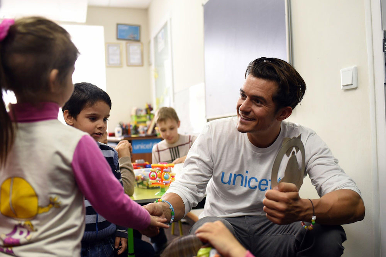 Orlando Bloom con alcuni dei 40 bambini che ogni giorno frequentano il centro ricreativo per bambini sfollati di Svjatogorsk (Ucraina) - ©UNICEF/UN017900/Georgiev