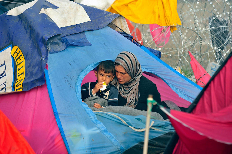 Una donna e il suo bambino all'ingresso della loro tenda a Idomeni, al confine tra Grecia e Macedonia - ©UNICEF/UN012799/Georgiev