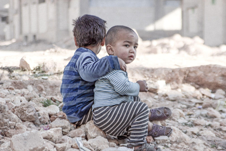 Esraa e Waleed, due fratellini di 4 e 3 anni, siedono fra le macerie di Aleppo, il giorno di Natale. Come 3,7 milioni di altri bambini siriani, non hanno mai vissuto un giorno di pace - ©UNICEF/ UN013172/Al-Issa