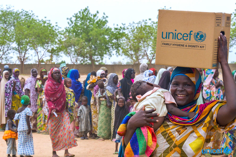 Una donna con un kit per l'igiene familiare che ha appena ricevuto  nel campo per sfollati di Maiduguri, Nigeria © UNICEF/UNI193739/Esiebo