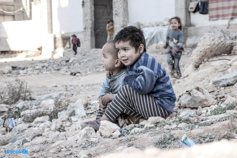 Due bambini seduti tra le macerie  © UNICEF/UN013175/Al-Issa
